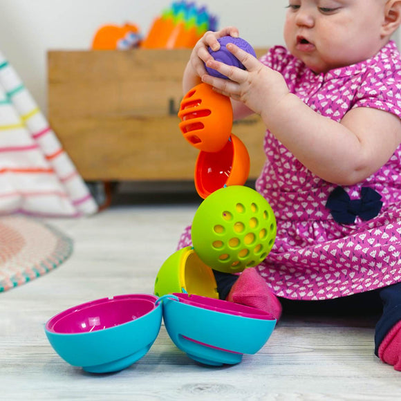 A brightly coloured Early learning toy . Multiple balls nest inside each other like a matrioshka doll. Each ball features a different textured surface.