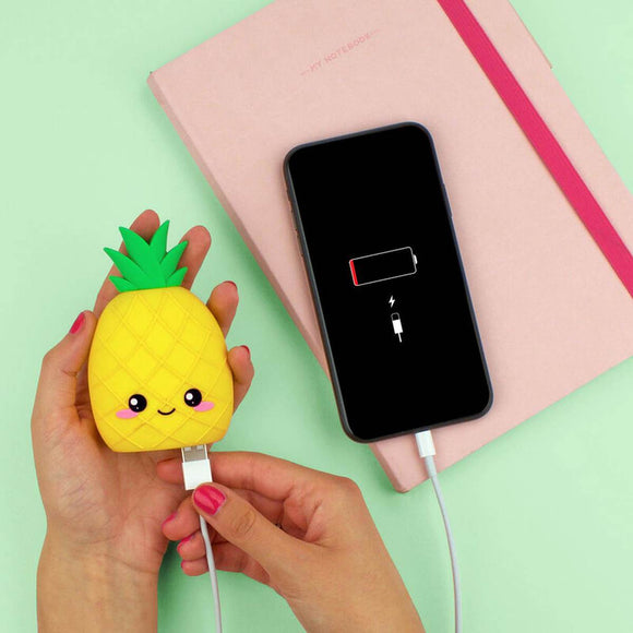Image featuring the pineapple power bank in the center which includes its USB power chord next to it, on the face of the pineapple it includes eyes, a smile and rosy cheeks