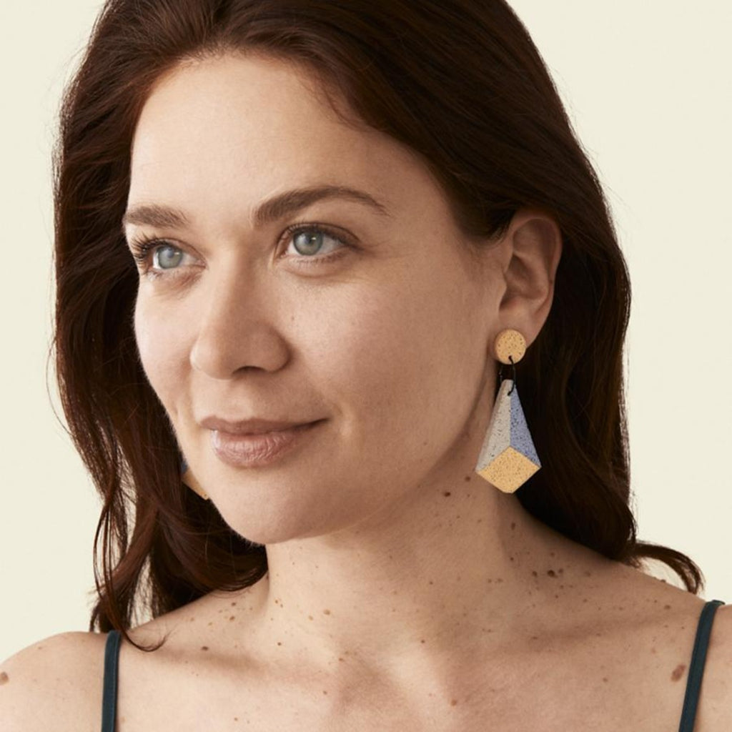 Image featuring a photograph of a woman with long brown hair wearing the retro art deco earrings
