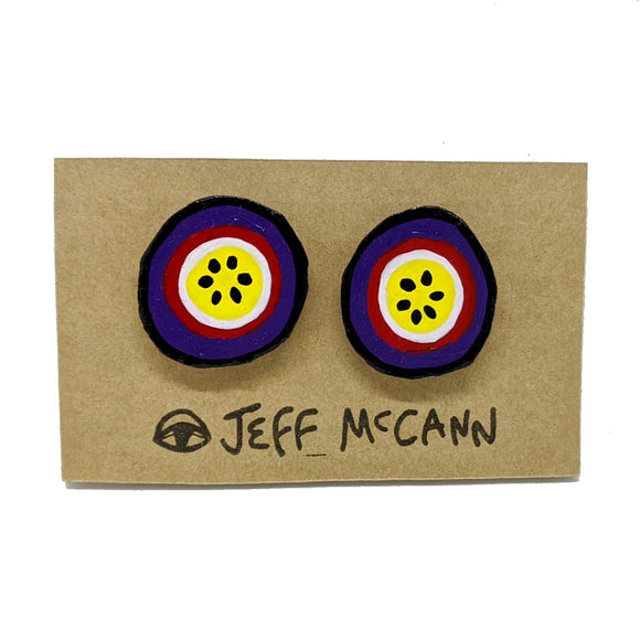 A Pair of stud Earrings made of hand painted cardboard. A design in the shape of a passionfruit cut open - in purple, red, yellow, white and black