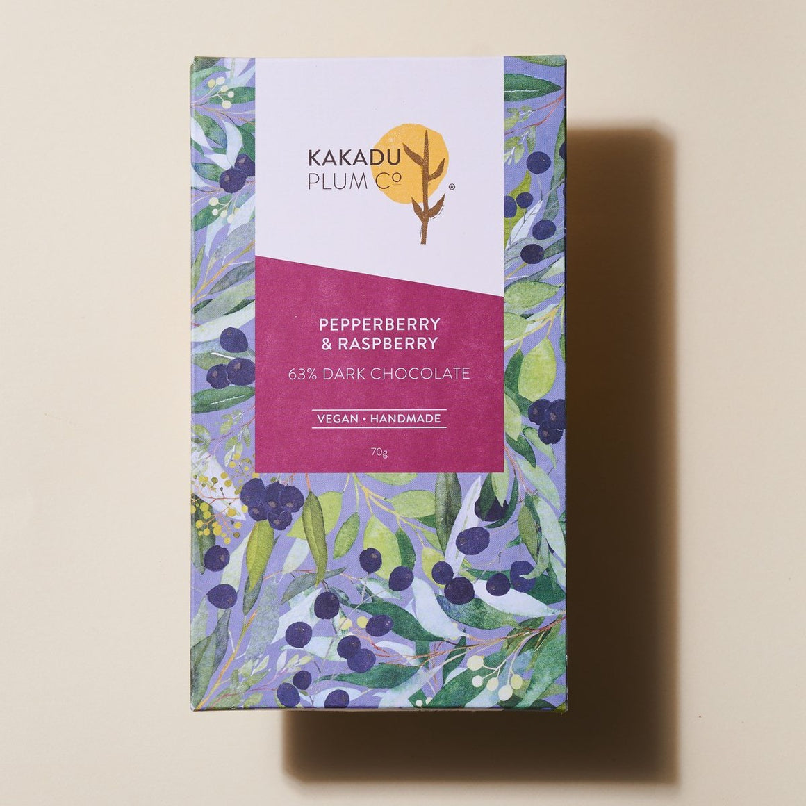 A Chocolate bar wrapped in paper with a print of Pepperberry plant. The Label reads Pepperberry & Raspberry, 63% Dark Chocolate, Vegan, Handmade, 70g