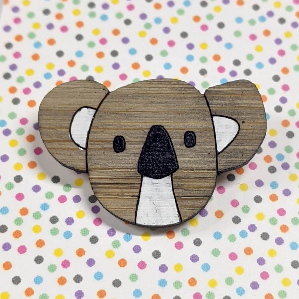A pin style brooch depicting a koalas head. Made from bamboo wood and hand painted. Shown on a polka dot background.
