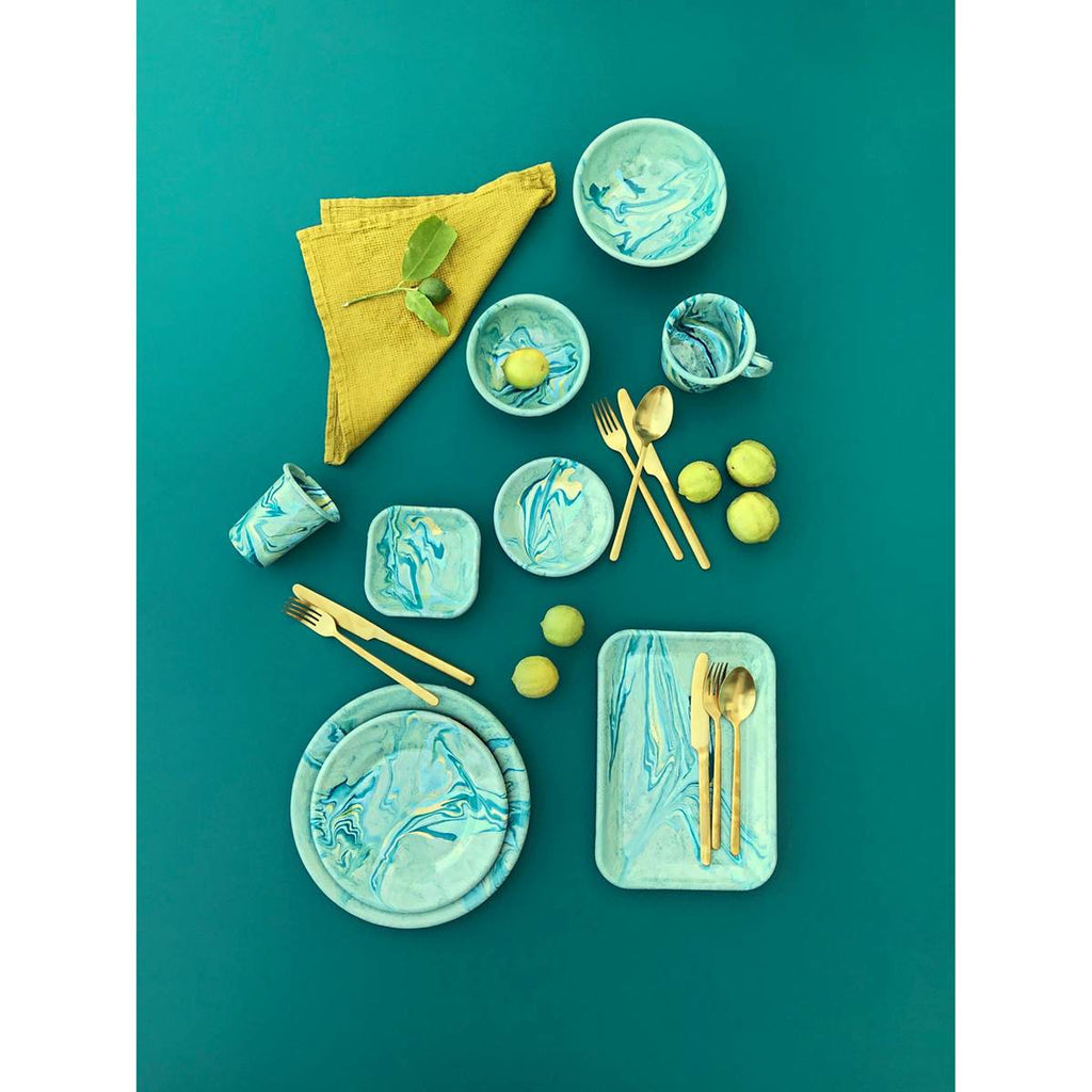 A range of enamel tablewear inclusing plates, bowls and mugs, on a turquoise background. Lemons, gold toned cutlery and a bright yellow napkin are used as props