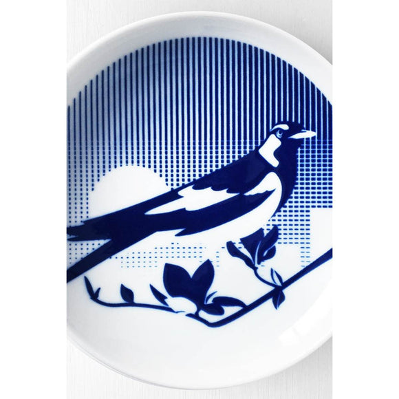 A Porcelain plate with a blue and white cobalt oxide glaze design on it. The design is a stylised image of a Magpie sitting on a branch in front of a skyline and sun