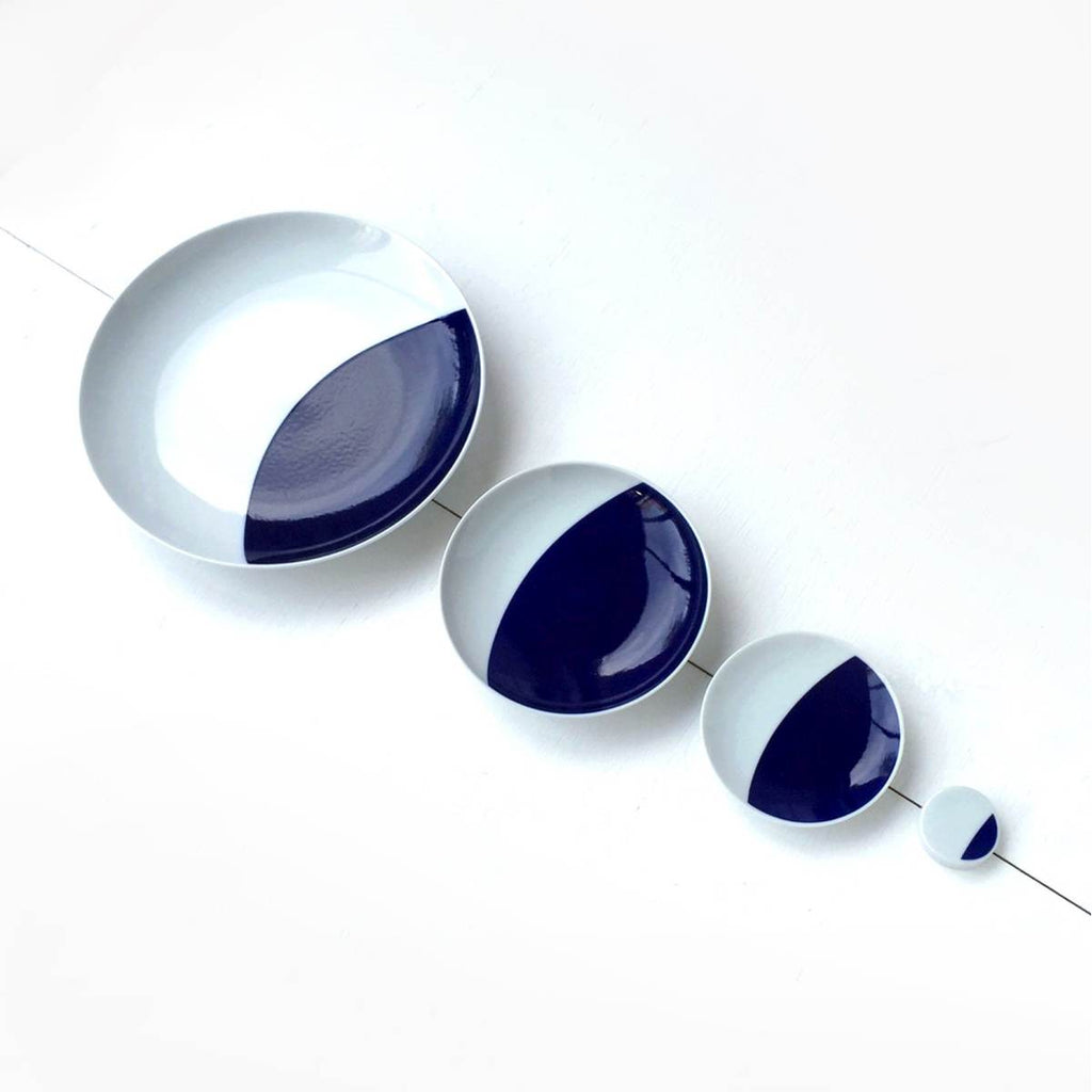 A set of 4 porcelain plates, in decreasing sizes,  with a blue and white cobalt oxide glaze design on them. The design is a abstract representation of the crescent moon, with a semicircle of blue on a black background.