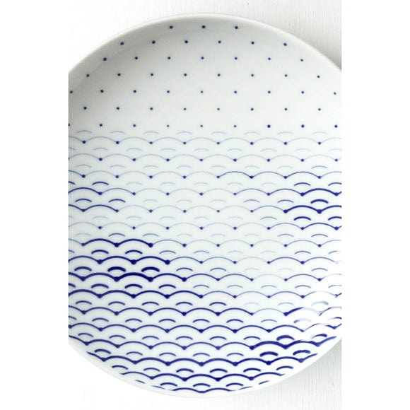 A Porcelain plate with a blue and white cobalt oxide glaze design on it. The design is a stylised abstract which mimics traditional japanese patterning while incorporating the WiFi symbol.