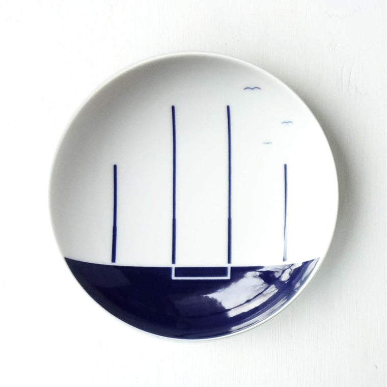 A Porcelain plate with a blue and white cobalt oxide glaze design on it. The design is a stylised set of Australian Rules Goalposts.