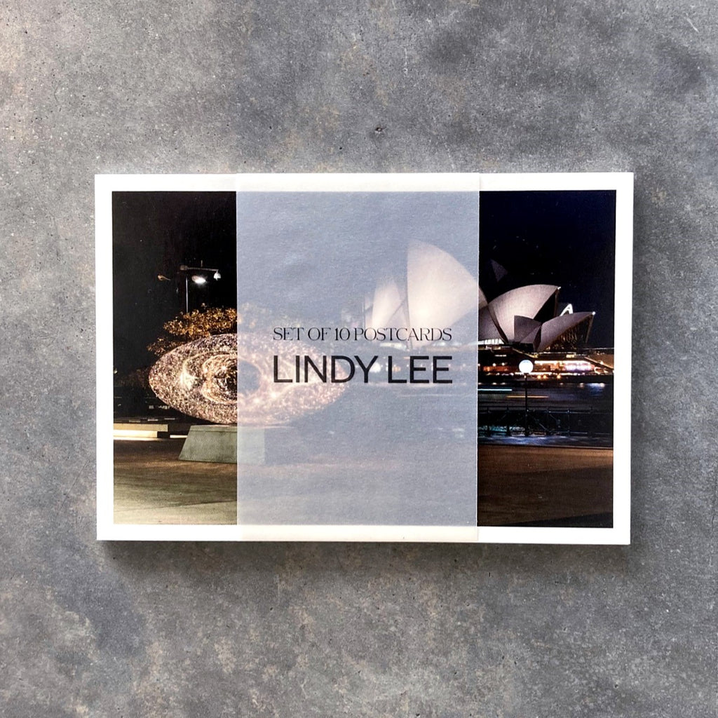 A pack of postcards featuring reproductions of Lindy Lee's artworks. The pack of 10 are held together by a semi translucent paper wrap