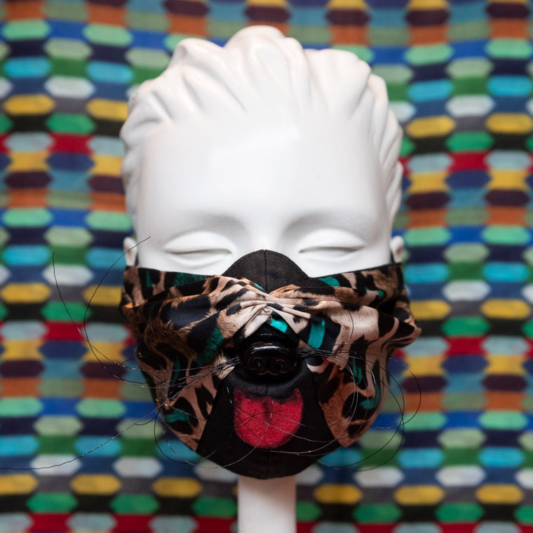 Mask featuring leopard print with turquoise spots fabric including wire whiskers, pink fabric tongue and a black plastic dog nose