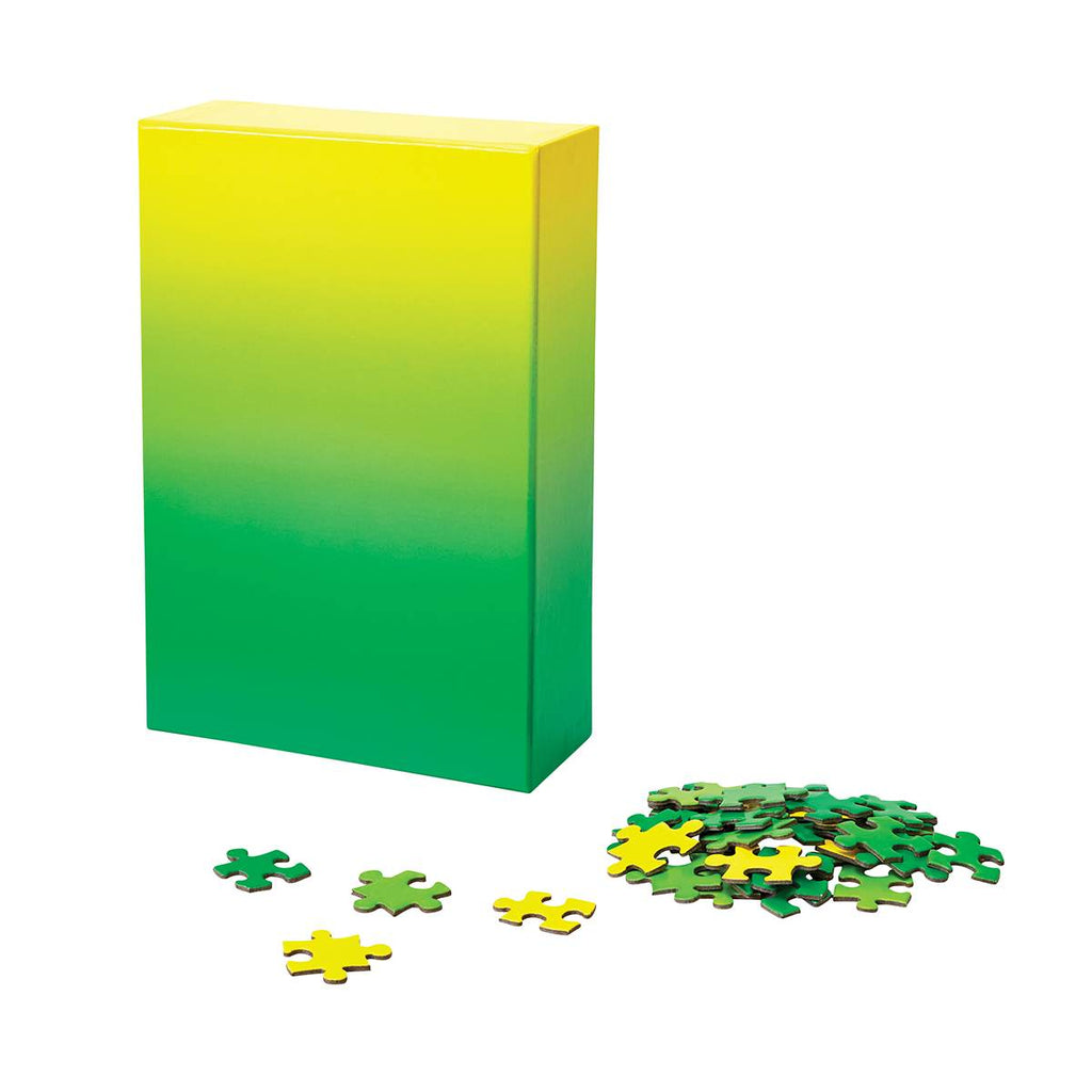 A puzzle in a tonal gradient from neon yellow to grass green. The image shows the puzzle box next to a pile of assorted puzzle pieces.