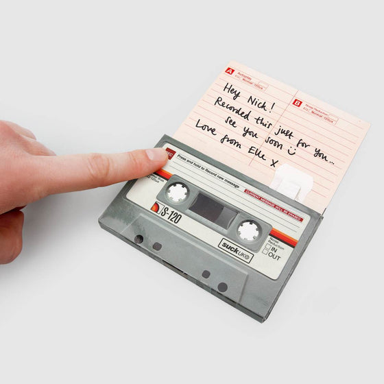 A cassette tape has been made into a greeting card, shown open with hand written greeting card message inside. A persons finger is pressing a  record button on the cassette tape to record a personalised message.