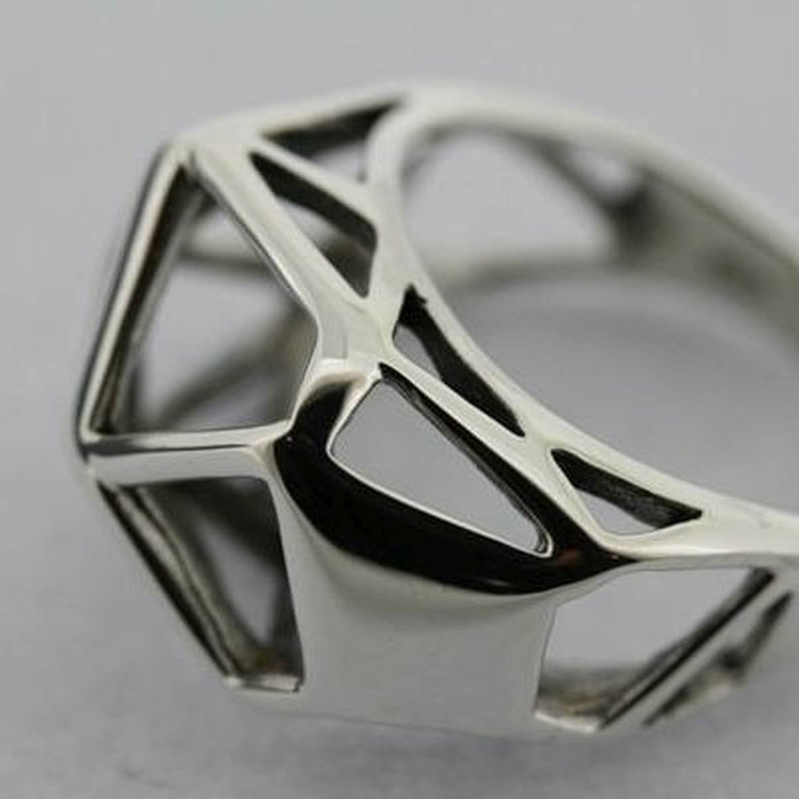A Silver Ring, featuring a larger, geometric form made of cut out triangles.