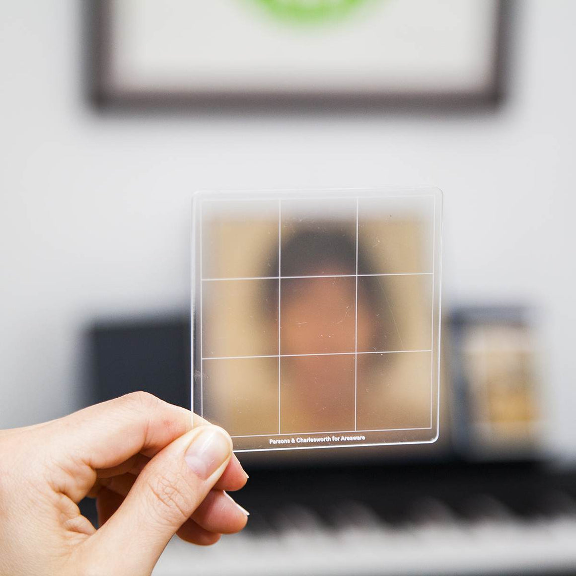 An translucent Artist tool marked with the Rule of thirds ratio. Shown being held up in front of a photo portrait