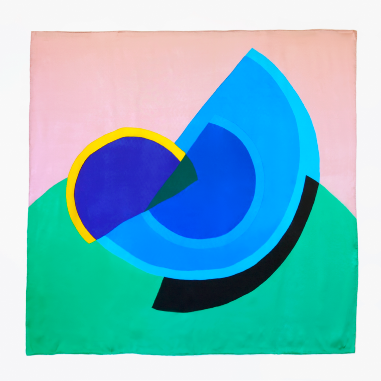 a Silk scarf , printed with an abstract artwork. Semi circular shapes in contrasting blues, yellow, green and black on a pastel pink background,