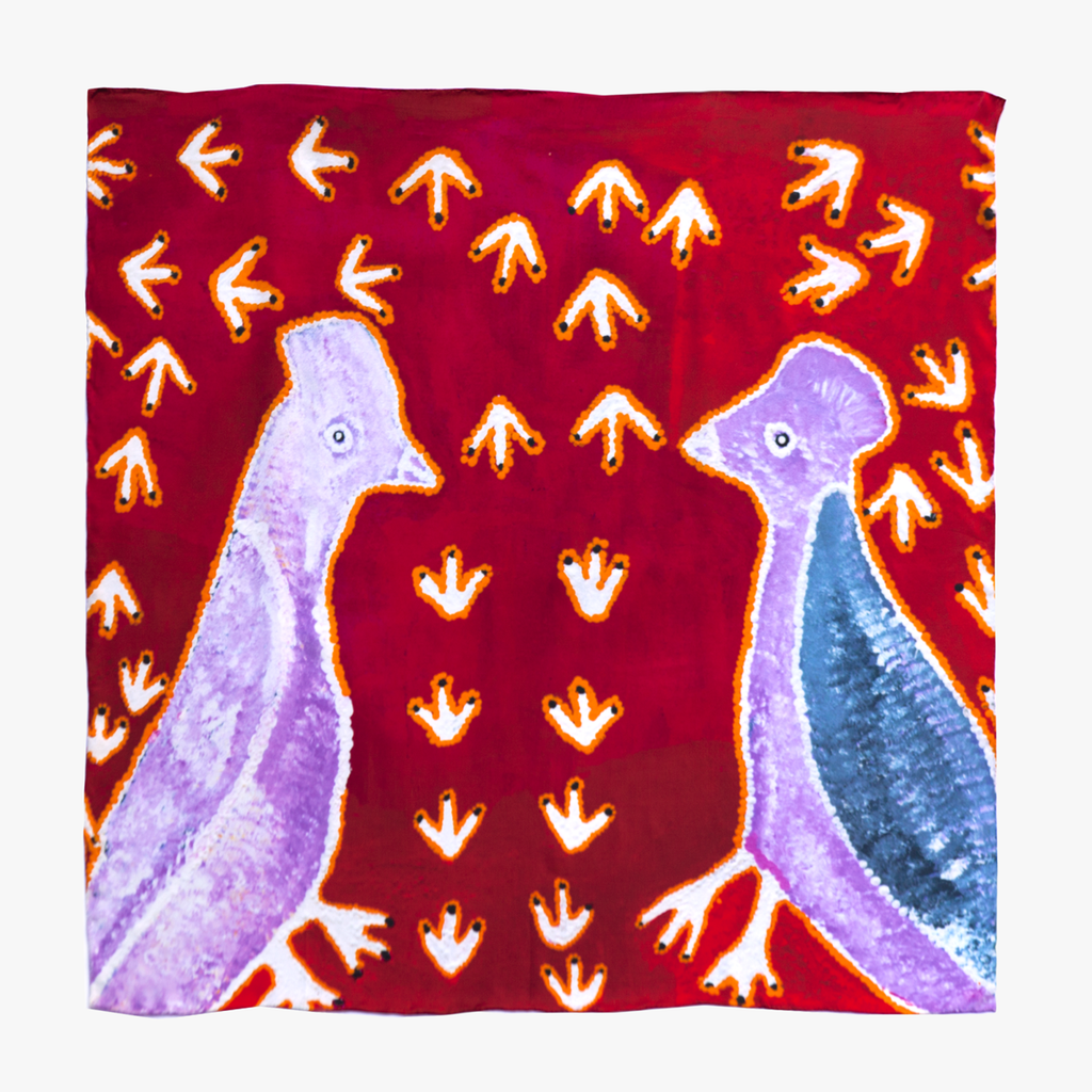 a Silk scarf , printed with an Aboriginal artwork. Two large stippled birds in pastel blue and purple tones, surrounded by white emu tracks on a rich red background.