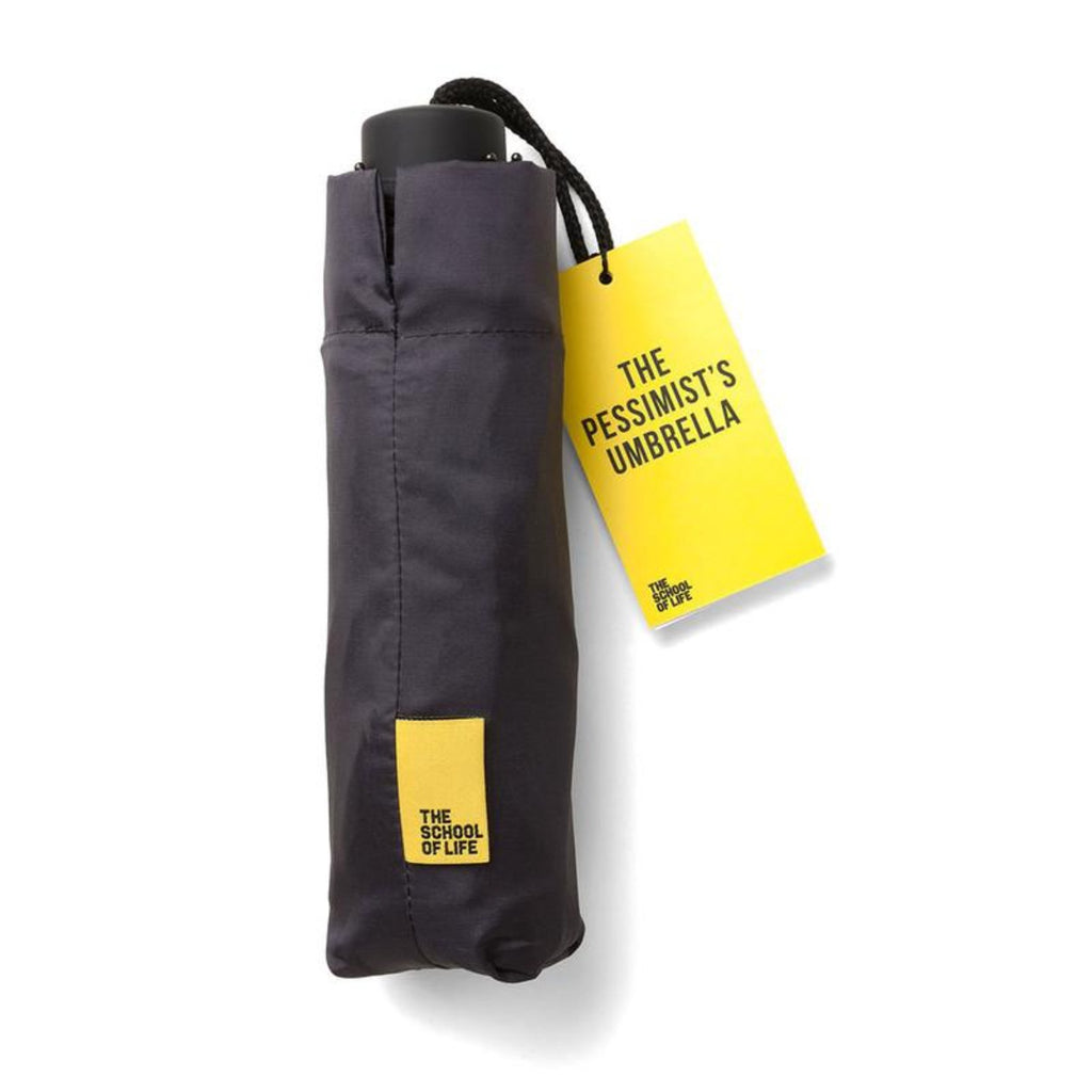 Image of a packaged umbrella which includes two swing tags, one featuring the words: the school of life and then the other featuring the words: The Pessimist's Umbrella