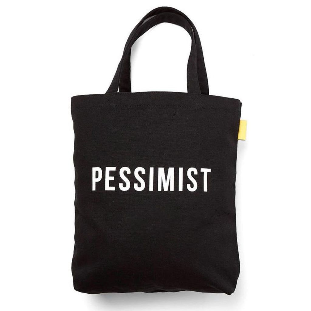 Image featuring a black canvas tote bag in the center with the word Pessimist in white font in the middle
