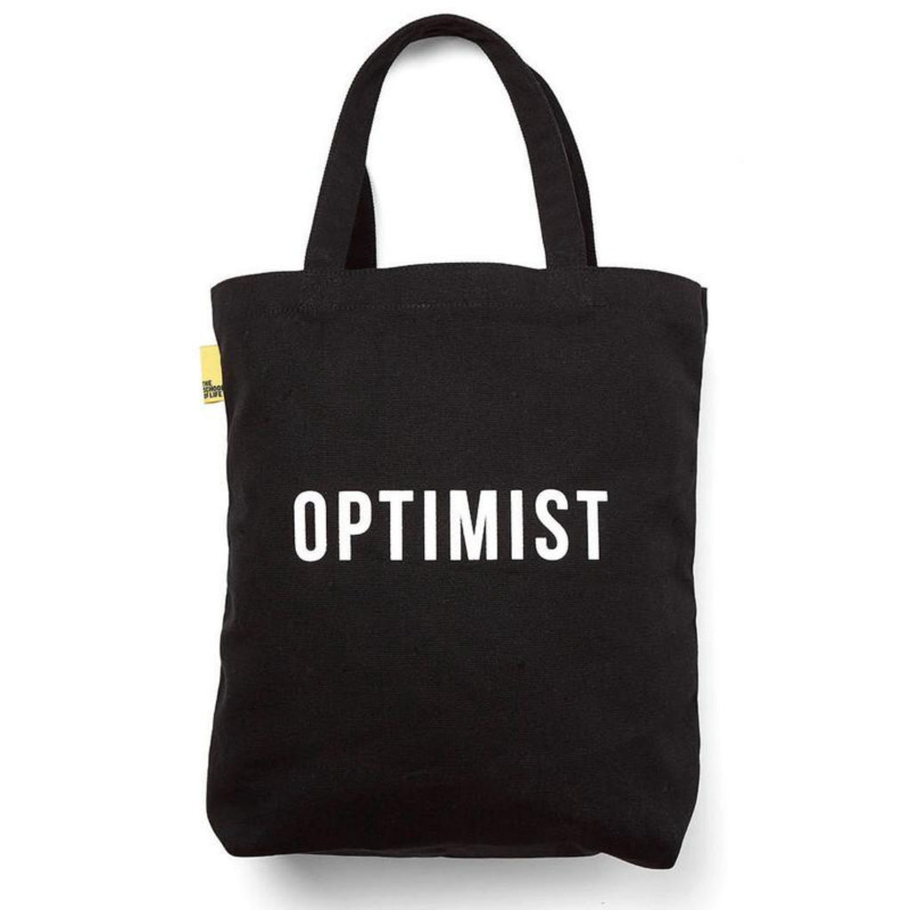 Image featuring a black canvas tote bag in the center with the word Optimist in a white font in the middle