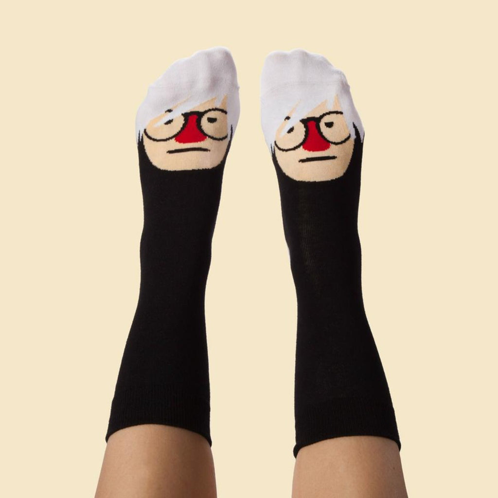 Image of a pair of feet which are wearing a pair of socks which feature a graphic illustration of andy warhol