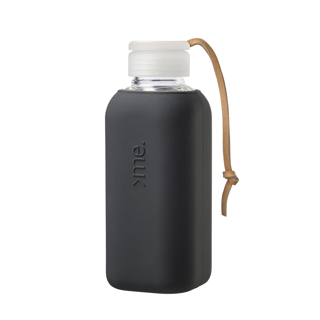 Image featuring a white background with a glass water bottle in centre which has a black silicone sleeved wrap around it, it also includes a cap and a leather strap