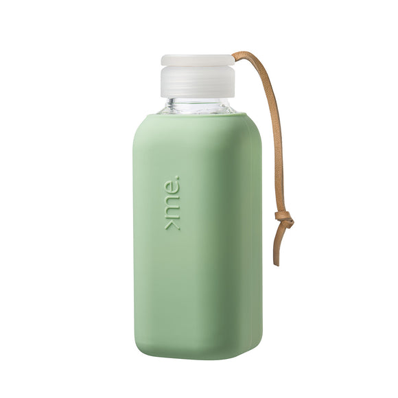 Image featuring a white background with a glass water bottle in centre which has a mint green silicone sleeved wrap around it, it also includes a cap and a leather strap