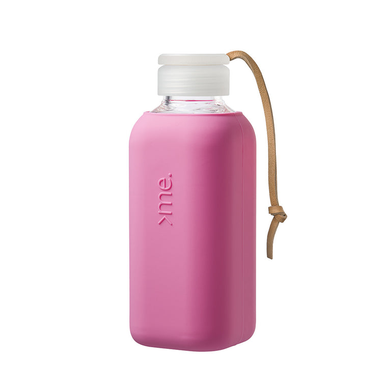 Image featuring a white background with a glass water bottle in centre which has a Raspberry Pink silicone sleeved wrap around it, it also includes a cap and a leather strap