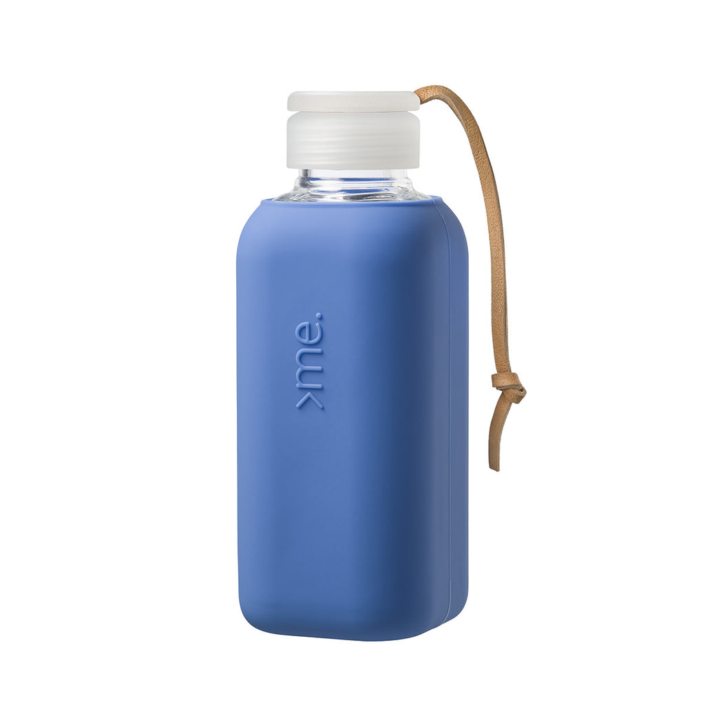 Image featuring a white background with a glass water bottle in centre which has a blue silicone sleeved wrap around it, it also includes a cap and a leather strap