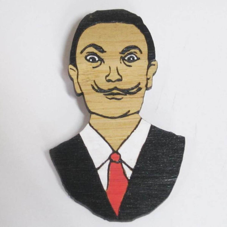 A brooch featuring a portrait of artist Salvador Dali. He is shown wearing a black suit and tie. .Made from bamboo wood and hand painted.