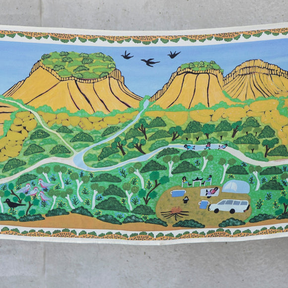 A long silk scarf is displayed by two women, holding the top corners. The scarf features the artwork artwork by Betty Conway depicting a mountain range, road, a camp, people, animals and plant life in greens, yellow, ochre, brown, olive and blue tones.