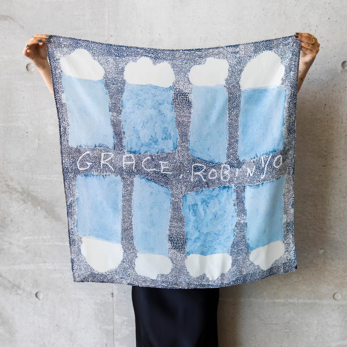 A square silk scarf is displayed by a woman, holding the top corners. The scarf feature the artwork Kwatye by Grace Robinya featuring clouds, rain and intricated dotwork in blue tones and white,
