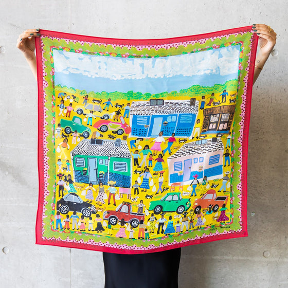 A square silk scarf is displayed by a woman, holding the top corners. The scarf features the artwork Titjikala by Doris Thomas and bright and colourful fecpition of life in community with people, cars, dogs and houses.lue tones and white,