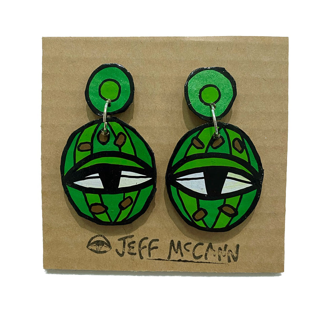 A pair of Jeff McCann drop earrings featuring an eyes and cactus inspired colours and shapes in green, brown, white and black.