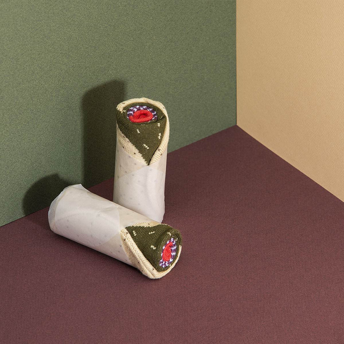 A pair of socks rolled and wrapped in paper to look like a burrito.