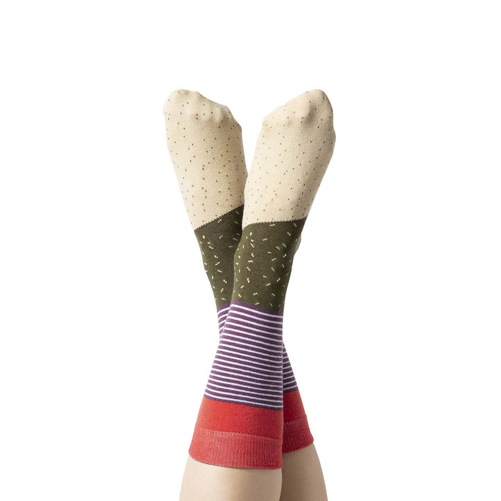 A model wears a pair of socks. The socks have multiple prints including white dots, green dashes and purple stripes.
