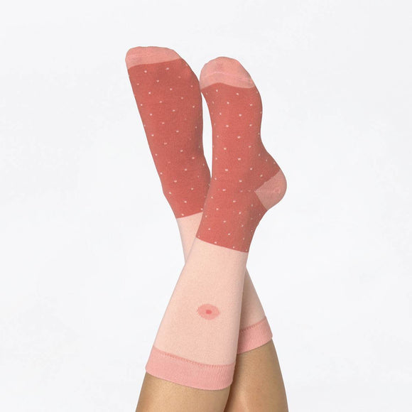 "A Pair of Printed socks in a box featuring a pink skin tone and nipple print. They are printed and rolled to look like a breast when packaged. The box shows the text ""Girl Power Socks"""