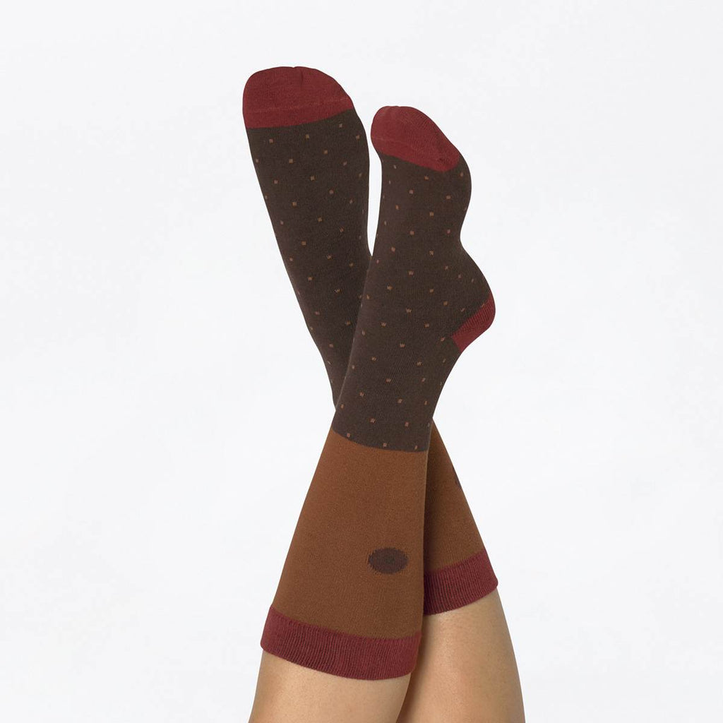 A model wears brown tone printed socks featuring spots, stripes and a nipple print,