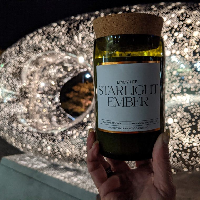 "A candle with the label ""Starlight Ember"" is held by a hand in front of the sculpture 'Secret World of a Starlight Ember'. The sculpture is lit up against a dark night sky."