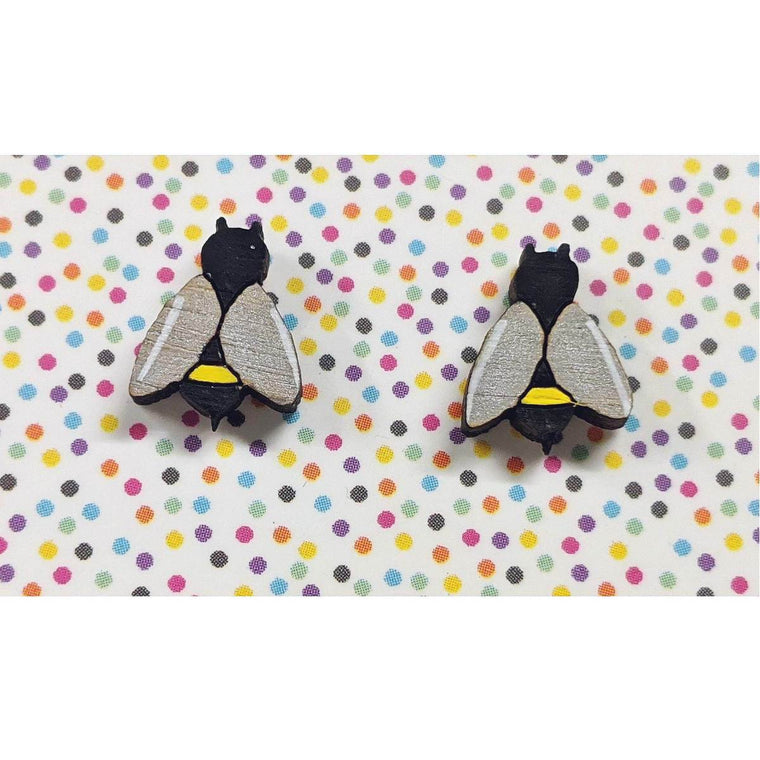 A pair of intricately hand coloured studs depicting honey bees. In yellow and black stripes, their wings are painted in a lustrous silver. Shown on a rainbow polka dot background.