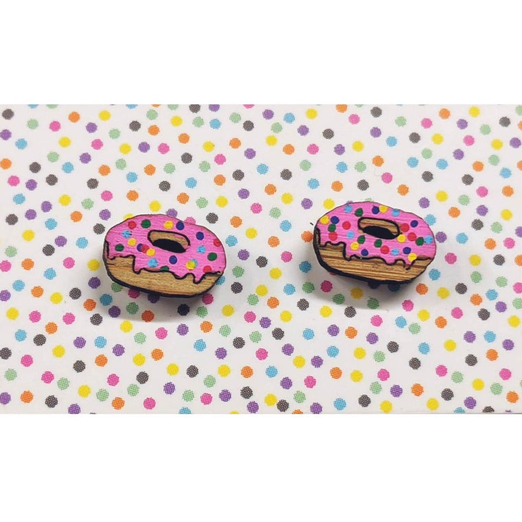 A pair of intricately hand coloured studs depicting pink iced donuts. The pink icing feature rainbow sprinkles. Shown on a rainbow polka dot background.