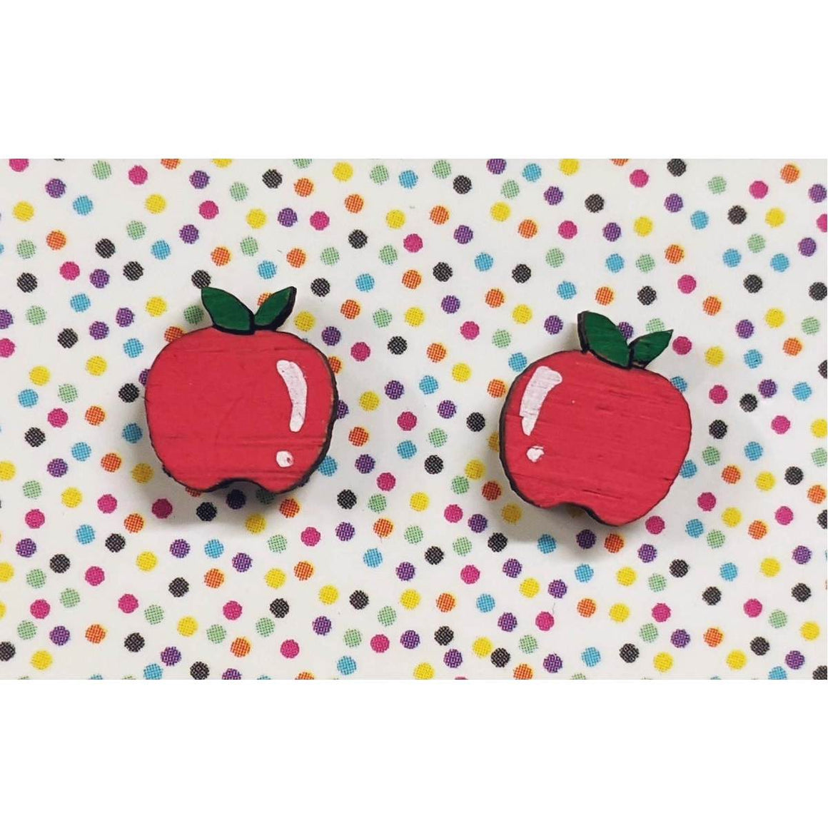 A pair of intricately hand coloured studs depicting rosy red apples with green leaves. The peeled layers hang down. Displayed on a rainbow polka dot background.