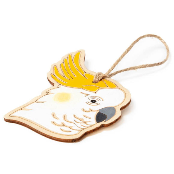 A hanging ornament in the form of a Sulphur-Crested Cockatoo. Laser Etched flat wood is adorned with white, grey, black and yellow hand painting. A Jute string is attached