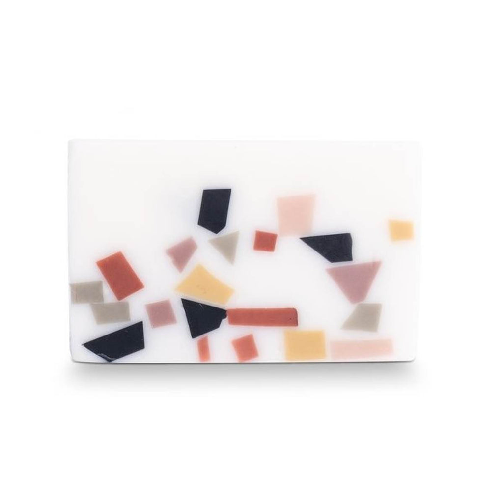 A white bar of soap, featuring a terrazzo finish in tones of black, white, pink, yellow and olive green