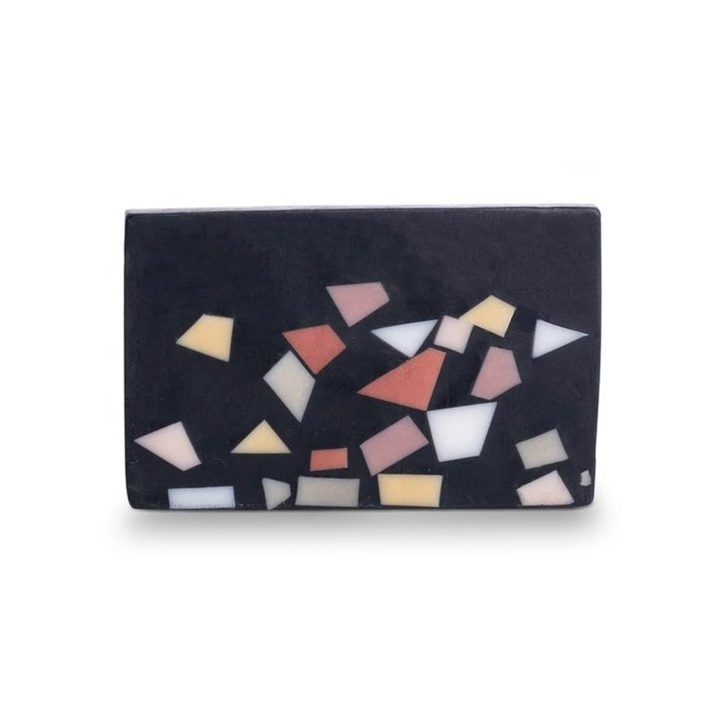 A black bar of soap, featuring a terrazzo finish in tones of black, white, pink, yellow and olive green