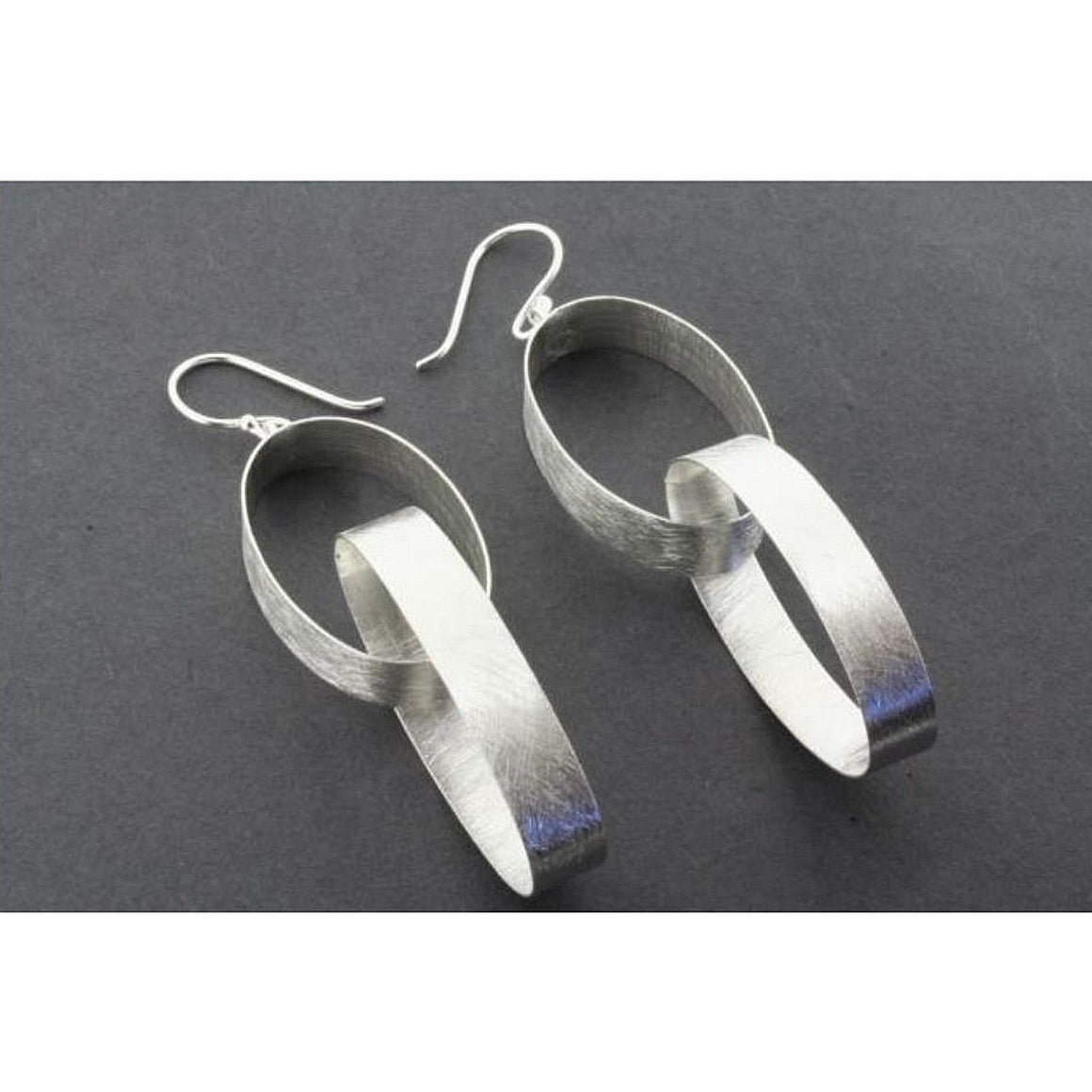 A pair sterling silver two hooped drop earrings sitting on top of a grey background