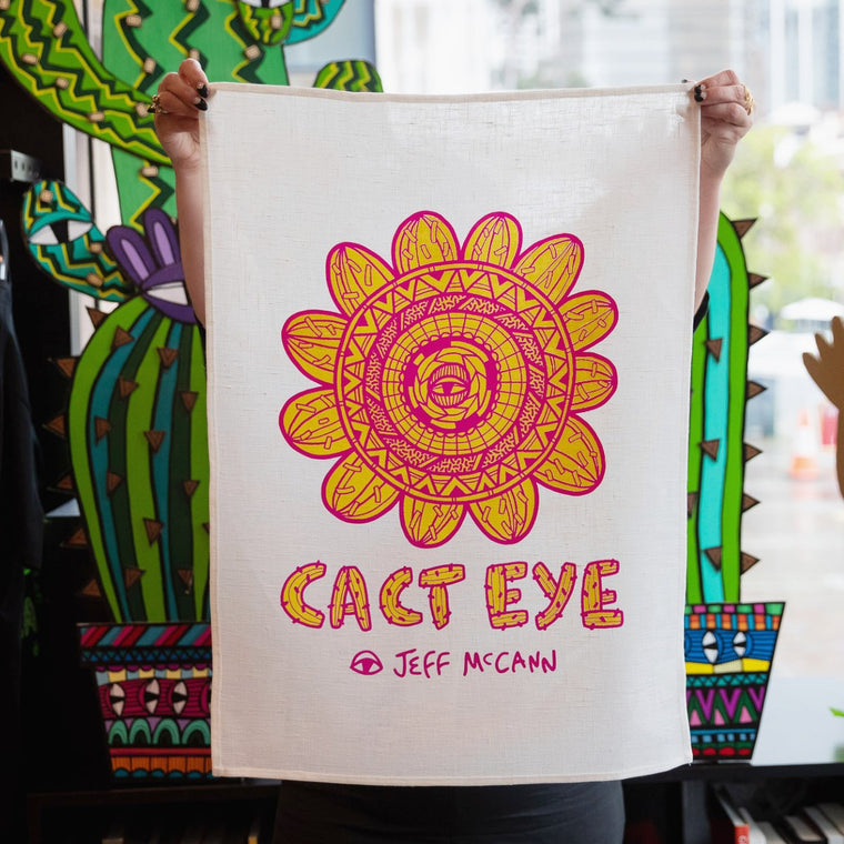 "A white Linen tea towel is shown behind held up by a woman. It features a bold circular Yellow and Pink work by Sydney artist Jeff McCann featuring eyes, cactuses, and bold abstract patterning. Text reads ""CACT EYE Jeff McCann"" in a Cactus inspired font."