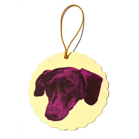 A Round Yellow hanging Air Freshener with an image of a Dachshund's head rendered in pink and black. A Orange hanging tag is attached.
