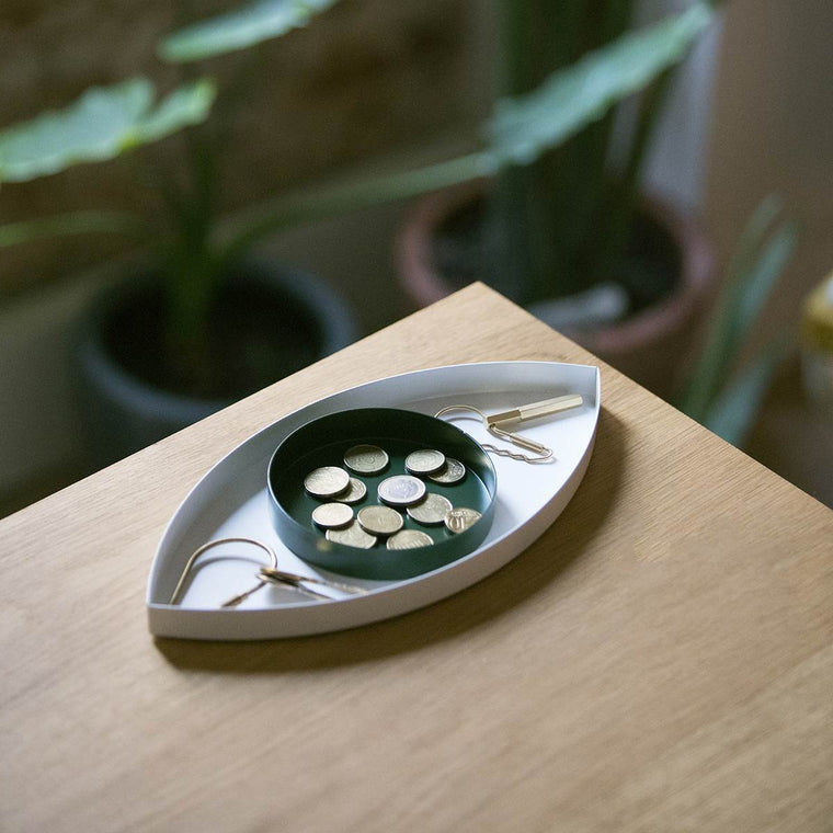 A tray set Crafted from metal consisting of two trays (a large white almond shape and a smaller green circular dish) that form a beautiful eye when overlaid. Shown in a domestic setting on a wooden table. Shown holding Keys and coins.