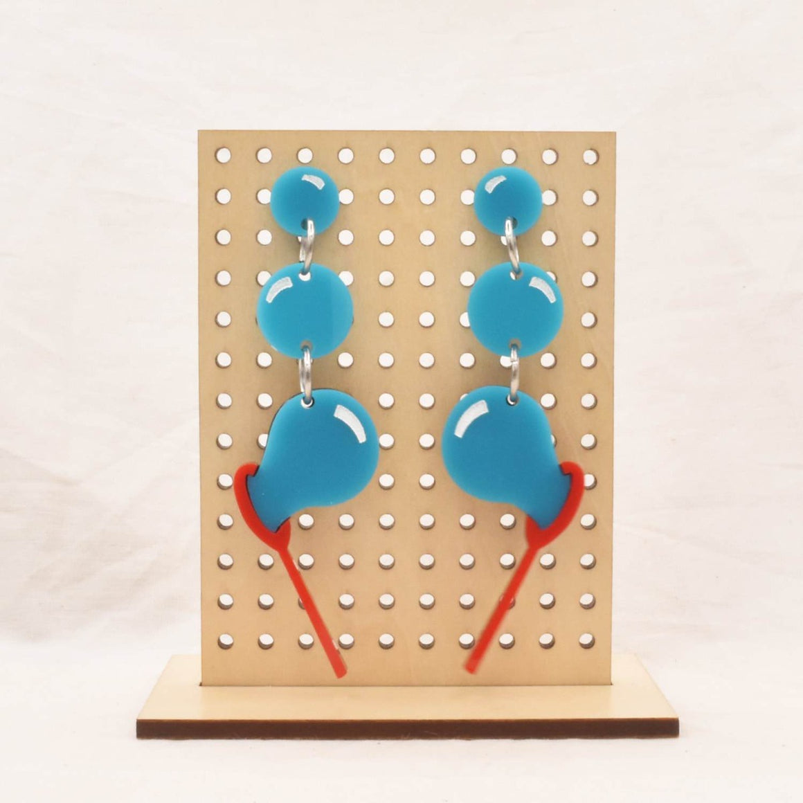 Image featuring a tanned wood stand holding two graphically illustrated earrings both featuring a row of blue bubble balloon with a red bubble blowing wand
