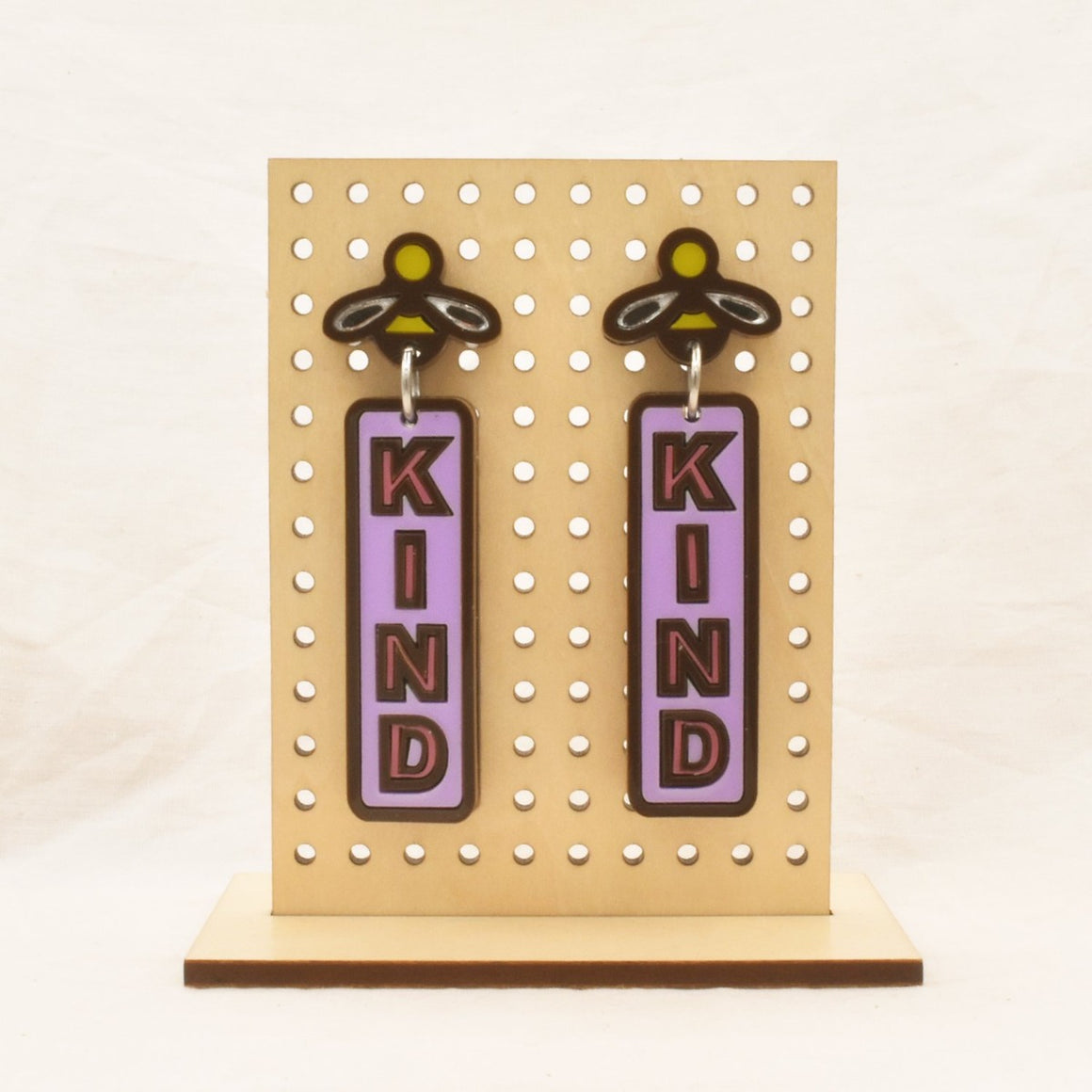 Image featuring a tanned wood stand holding two graphically illustrated earrings both featuring a bee on the top and then the word Kind