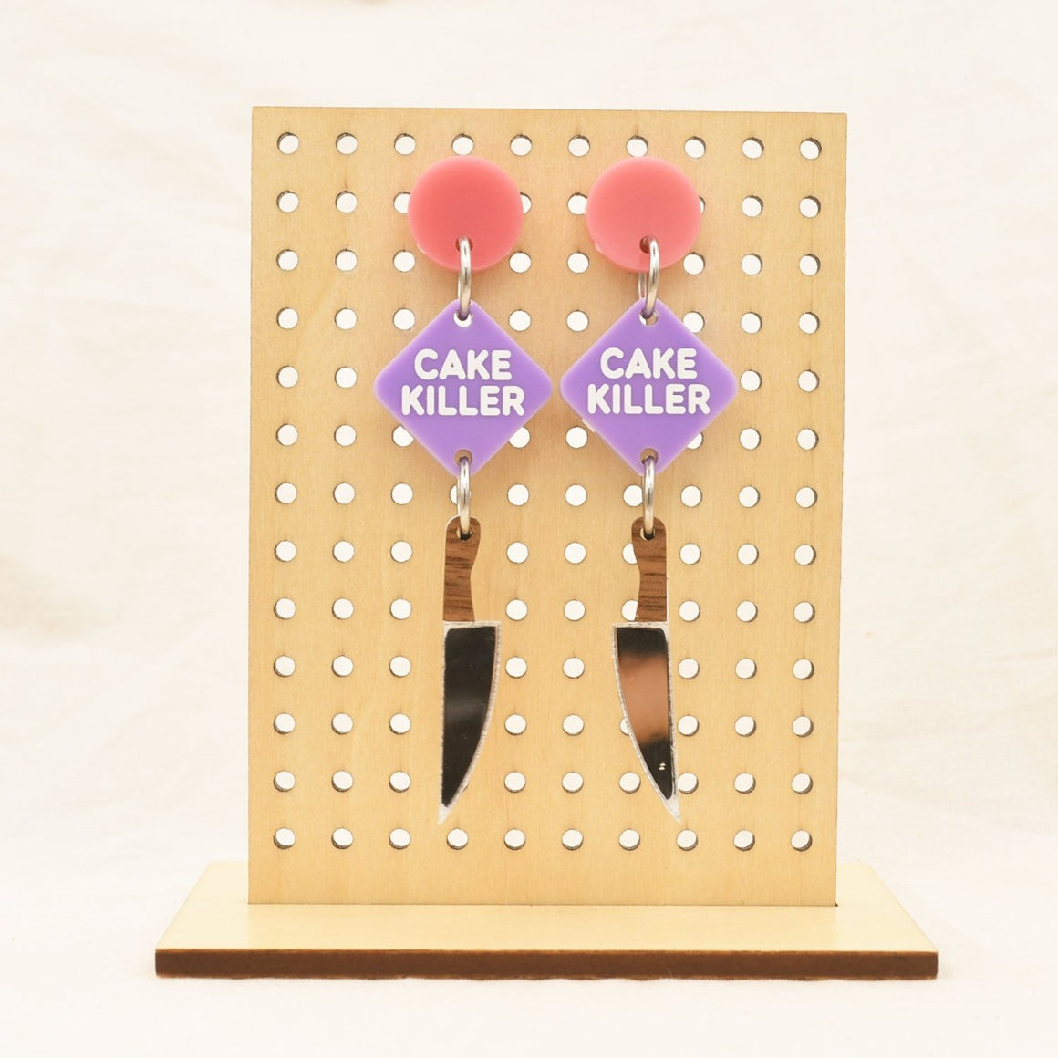 Image featuring a tanned wood stand holding two graphically illustrated earrings both featuring a pink circle, purple square with the words Cake Killer on them and then a knife below